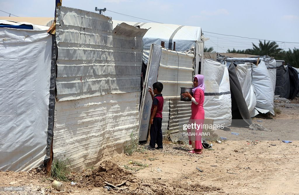 Displaced Iraqis are seen May 31, 2016 at the Alexanzan camp in the Dora neighbourhood on the southern outskirts of Baghdad, where they are taking shelter after they were displaced from the Jbeil, a village near the embattled Iraqi city of Fallujah due to clashes between pro-government forces and the Islamic State (IS) group. Only a few hundred families have managed to slip out of the Fallujah area ahead of the assault on the city, with an estimated 50,000 civilians still trapped inside, sparking fears the jihadists could try to use them as human shields. ARAR