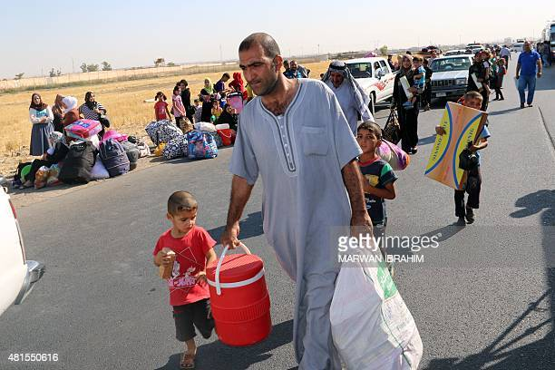Displaced Iraqis carry their belongings before boarding vehicles to return home to the city of Tikrit in areas that were retaken by security forces...
