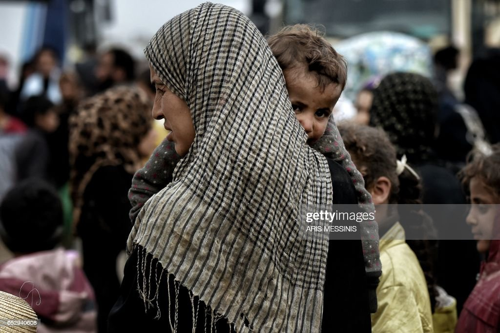 TOPSHOT - Displaced Iraqis from Mosul arrive at the Hamam al-Alil camp on March 13, 2017, during the government forces ongoing offensive to retake the western parts of the city from Islamic State (IS) group fighters. /