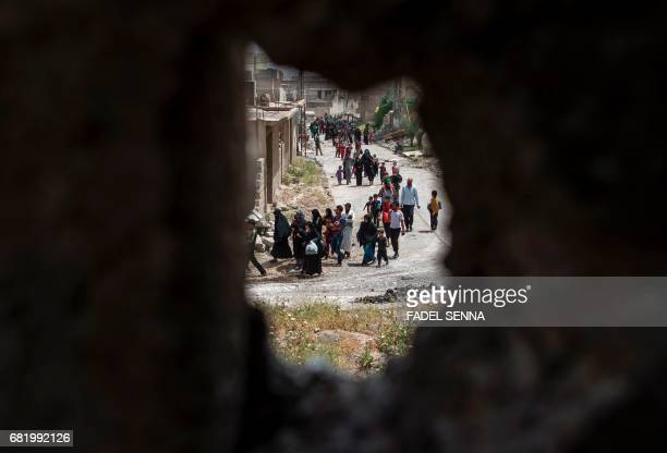 TOPSHOT Displaced Iraqis from Mosul's northwestern alHaramat neighbourhood flee their homes on May 11 2017 as government forces advance in their...
