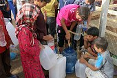 Displaced Iraqis from the embattled city of Fallujah fill bottles of water at a camp where they are taking shelter some 30 kilometres on the southern...