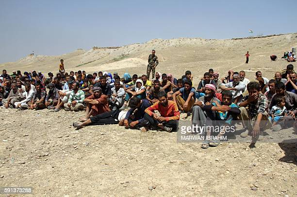 Displaced Iraqis from the northern Iraqi village of Hawija rest under the protection of Peshmerga forces some 50 kilometres north west of Kirkuk...