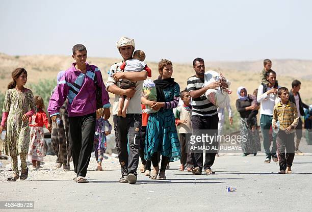 Displaced Iraqis from the Yazidi community carry their children as they cross the IraqiSyrian border at the Fishkhabur crossing in northern Iraq on...