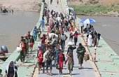 Displaced Iraqis from the Yazidi community cross the IraqiSyrian border along the Fishkhabur bridge over the Tigris River at the Fishkhabur crossing...