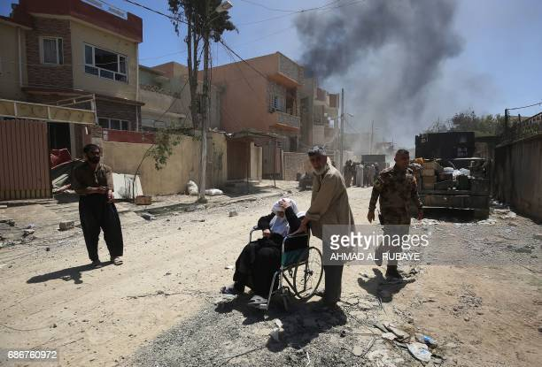 TOPSHOT Displaced Iraqis from West Mosul's AlNajjar neighbourhood leave their homes on May 22 during the ongoing offensive by security forces to...