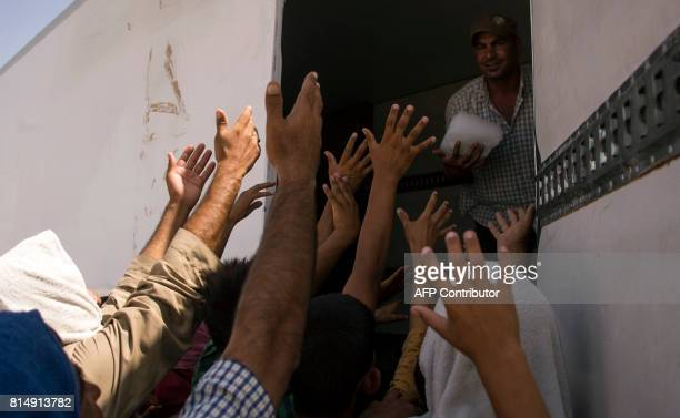Displaced Iraqis gather to receive ice at a camp set up to shelter civilians fleeing violence in the northern city of Mosul on July 15 2016 in Debaga...