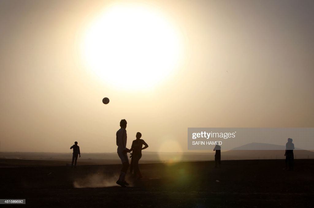 Displaced Iraqis play football at sunset at a temporary camp set up by the UN refugee agency to shelter people fleeing violence in northern Iraq, on July 1, 2014, in Aski Kalak, 40 kms west of the Kurdish autonomous region's capital Arbil. Saudi Arabia pledged $500 million in humanitarian aid for Iraq to be disbursed through the United Nations to those in need regardless of sect or ethnicity, state media reported.