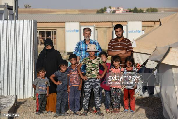 CORRECTION Displaced Iraqis pose for a photograph at the Hasan Sham camp for internally displaced people on June 10 2017 / AFP PHOTO / MOHAMED...
