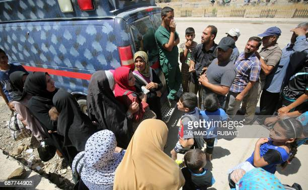 Displaced Iraqis queue up to receive food aid packages in western Mosul on May 24 during the ongoing offensive to retake the area from Islamic State...