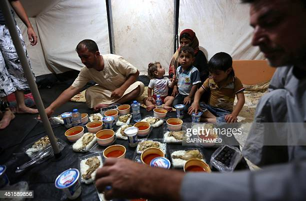 Displaced Iraqis ready to break their fast during the holy Muslim month of Ramadan as they sit in a tent provided by the UN refugee agency at a...