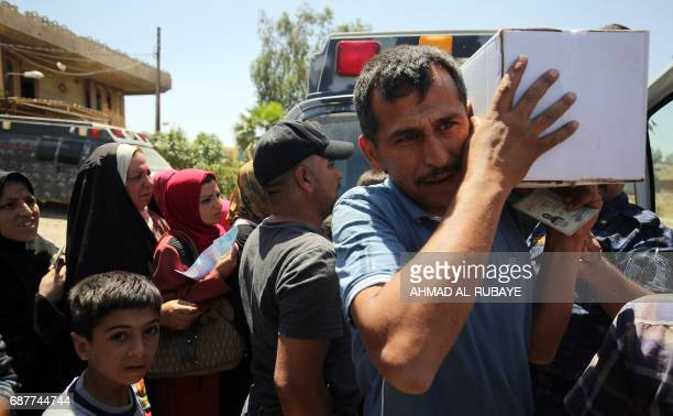 Displaced Iraqis receive food aid packages in western Mosul on May 24 during the ongoing offensive to retake the area from Islamic State group...