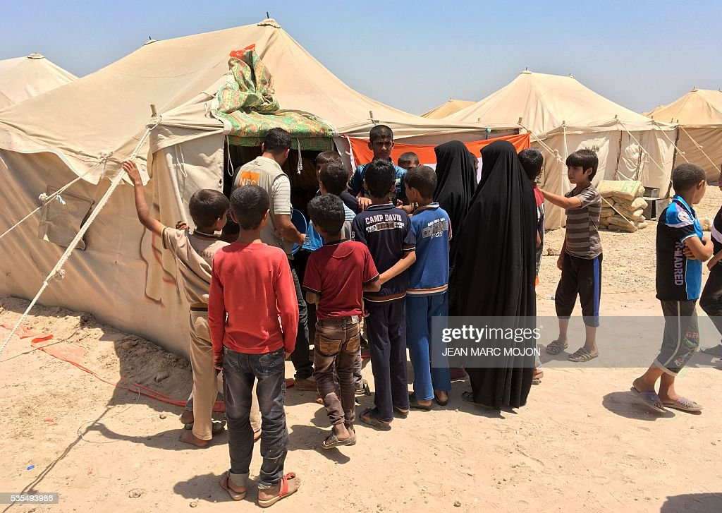 Displaced Iraqis register their families at the entrance of a newly-opened camp in the government-held town of Amriyat al-Fallujah 50 kilometres (30 miles) southwest of Baghdad, on May 29, 2016, which was set up to shelter people fleeing violence around the city of Fallujah. The Norwegian Refugee Council, which runs the camp in Amriyat al-Fallujah, says around 3,000 people have managed to flee the area and reach displacement camps since Iraqi forces launched an operation against the Islamic State a week ago. The biggest wave of arrivals so far was Saturday night and included mostly exhausted and hungry women and children. / AFP / Jean Marc MOJON
