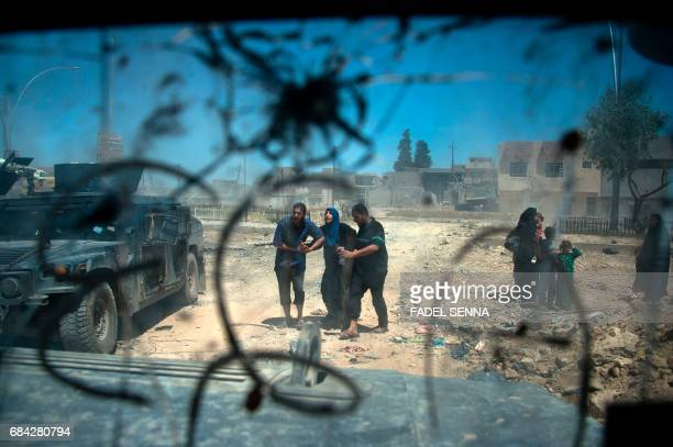 TOPSHOT Displaced Iraqis walk after evacuating their homes in a neighbourhood of west Mosul on May 17 during an ongoing offensive from the Iraqi...
