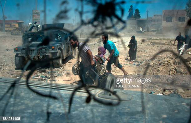 Displaced Iraqis walk after evacuating their homes in a neighbourhood of west Mosul on May 17 during an ongoing offensive from the Iraqi forces to...