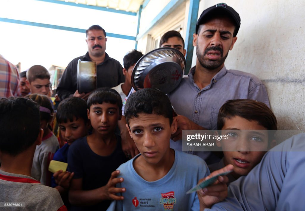 Displaced Iraqis who fled fighting between government forces and the Islamic State (IS) group in Anbar province line up to collect donated food at the Alexanzan camp in the Dora neighbourhood on the southern outskirts of Baghdad on May 31, 2106. Only a few hundred families have managed to slip out of Anbar's Fallujah area ahead of the assault on the city, with an estimated 50,000 civilians still trapped inside, sparking fears the jihadists could try to use them as human shields ARAR