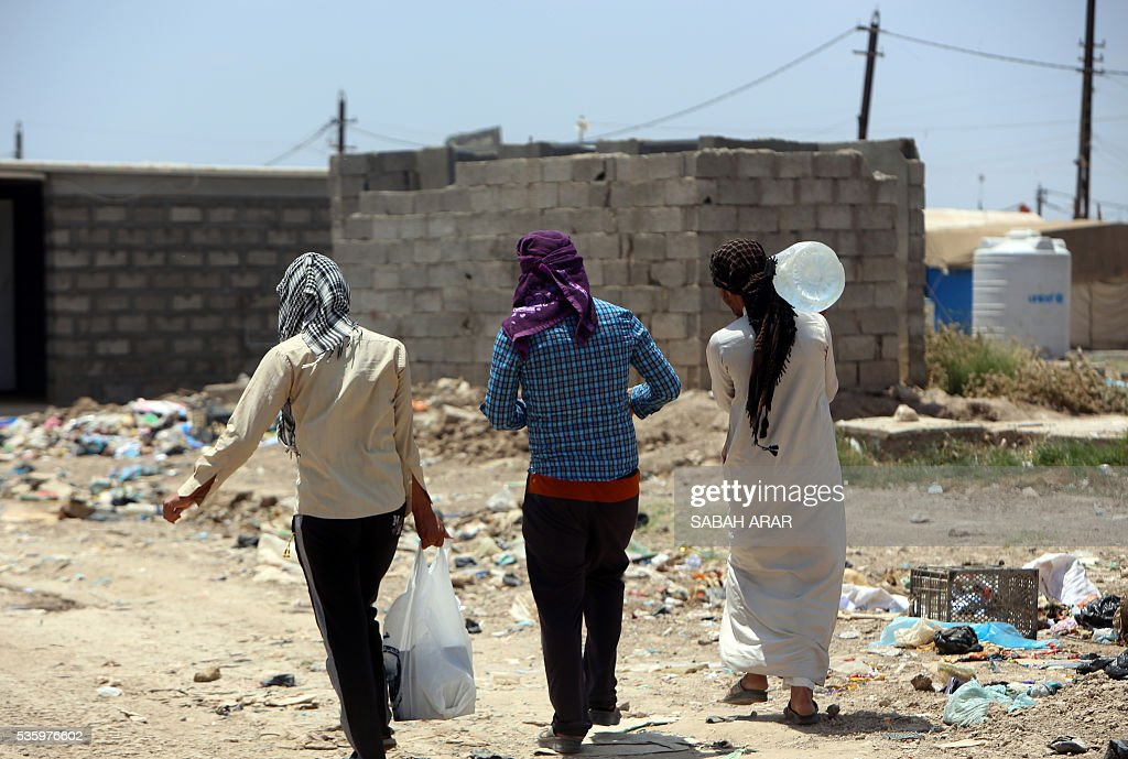 Displaced Iraqis who fled fighting between government forces and the Islamic State (IS) group in Anbar province walk caryying their goods on May 31, 2015 at the Alexanzan camp in the Dora neighbourhood on the southern outskirts of Baghdad on May 31, 2106. Only a few hundred families have managed to slip out of Anbar's Fallujah area ahead of the assault on the city, with an estimated 50,000 civilians still trapped inside, sparking fears the jihadists could try to use them as human shields ARAR