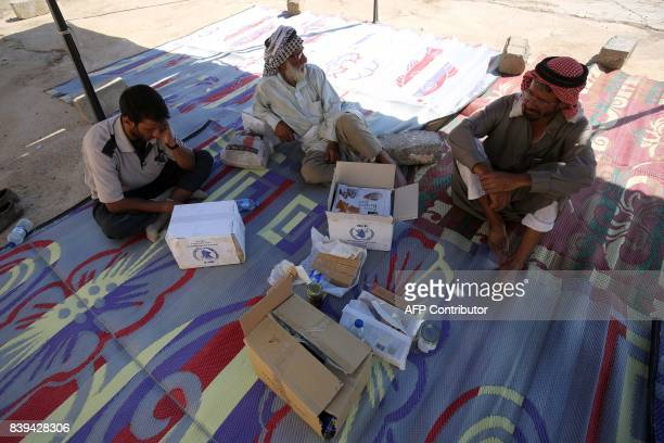 Displaced Iraqis who fled the fight between Iraqi forces and the Islamic State group in Tal Afar sit inside a tent next to boxes of medical aid at...
