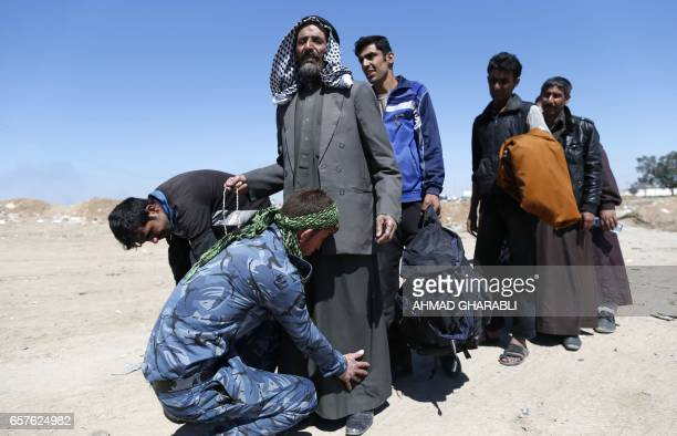 TOPSHOT Displaced Iraqis who fled their homes due to the ongoing fighting between government forces and Islamic State group fighters are checked as...
