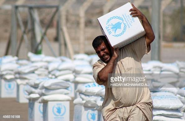 Displaced Iraqis who fled their homes following an offensive led by the Islamic State jihadist group collect boxes of food donated by the World Food...