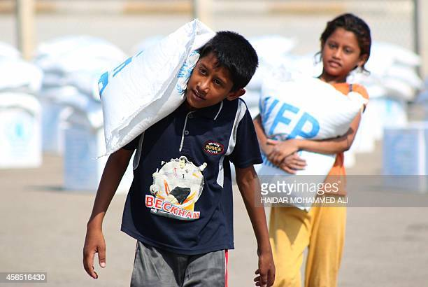 Displaced Iraqis who fled their homes following an offensive led by the Islamic State jihadist group collect sacs of food donated by the World Food...