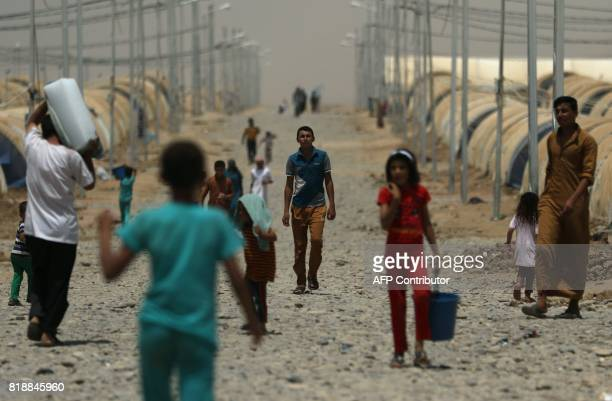 TOPSHOT Displaced Iraqis who had fled the violence around the northern Iraqi city of Mosul as a result of a planned operation to retake the Iraqi...