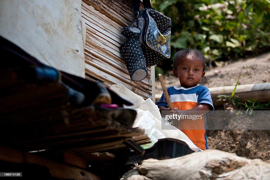 A displaced Nasa indigenous child is seen in a settlement in a mountainous area in Cali, Valle del Cauca department, Colombia, on April 13, 2013. The ONIC (National Indigenous Organization of Colombia) estimates that in 2011 there was a displacement of 5327 indigenous people, this amount was doubled in 2012. The ONIC warning calls, in its accounts of indigenous people in Colombia, that they are on the verge of extinction, due to the assassination of its members and the forced displacement towards urban areas brought on by fighting between armed groups. The total indigenous population in Colombia is estimated at 1.4 million, 3.4% of the country's population. AFP PHOTO/Luis ROBAYO