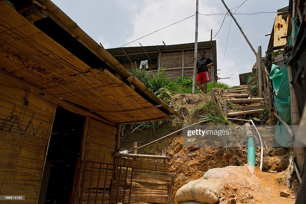 A displaced Nasa indigenous man is seen in a settlement in a mountainous area in Cali, Valle del Cauca department, Colombia, on April 13, 2013. The ONIC (National Indigenous Organization of Colombia) estimates that in 2011 there was a displacement of 5327 indigenous people, this amount was doubled in 2012. The ONIC warning calls, in its accounts of indigenous people in Colombia, that they are on the verge of extinction, due to the assassination of its members and the forced displacement towards urban areas brought on by fighting between armed groups. The total indigenous population in Colombia is estimated at 1.4 million, 3.4% of the country's population. AFP PHOTO/Luis ROBAYO