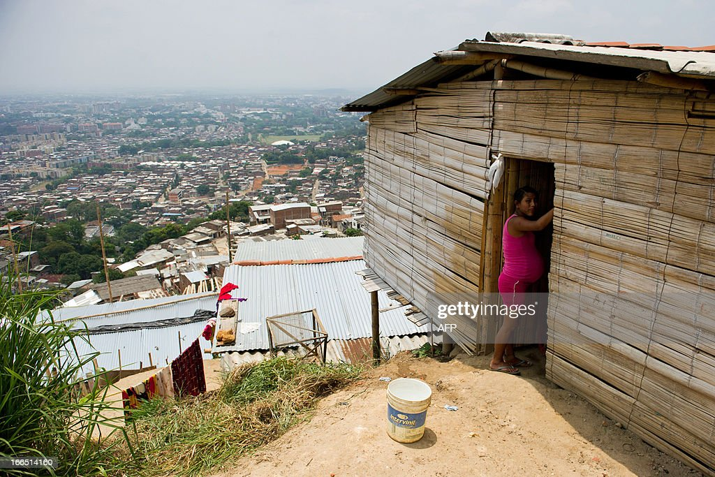 A displaced Nasa indigenous woman is seen in a settlement in a mountainous area in Cali, Valle del Cauca department, Colombia, on April 13, 2013. The ONIC (National Indigenous Organization of Colombia) estimates that in 2011 there was a displacement of 5327 indigenous people, this amount was doubled in 2012. The ONIC warning calls, in its accounts of indigenous people in Colombia, that they are on the verge of extinction, due to the assassination of its members and the forced displacement towards urban areas brought on by fighting between armed groups. The total indigenous population in Colombia is estimated at 1.4 million, 3.4% of the country's population. AFP PHOTO/Luis ROBAYO