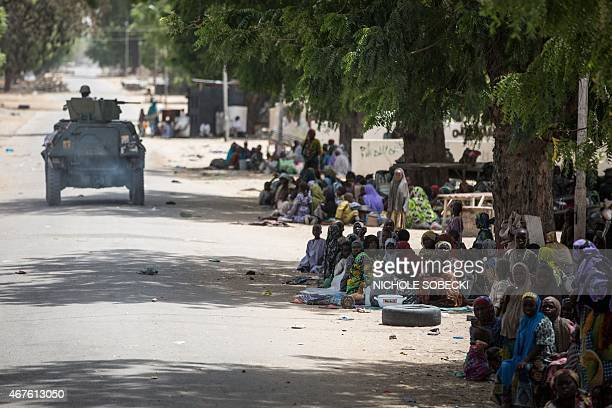 Displaced Nigerians sit on the side of a road in Bama on March 25 2015 after the army took over the town Nigeria's military has retaken the...