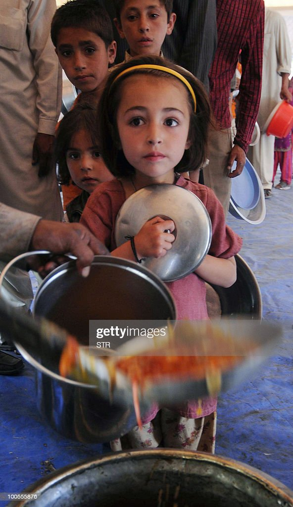 Displaced Pakistani children queue for food at a makeshift camp in Hunza district in a remote Himalayan region some 750 kilometres (450 miles) north of Islamabad, on May 25, 2010. An artificial lake which emerged on January 4, as a result of a massive landslide that killed 20, left about 25,000 people stranded and blocked the Hunza river in a remote Himalayan region. Flooding from the lake risks affecting 40,000 people with residents from up to 34 villages already evacuated to safety.