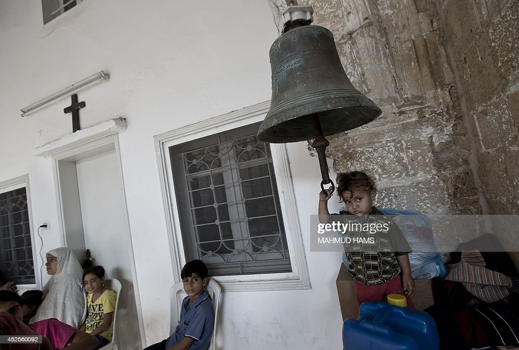 Displaced Palestinian children sit in a Greek Orthodox church where many Palestinians are taking shelter in Gaza City on July 23 2014 For the first...