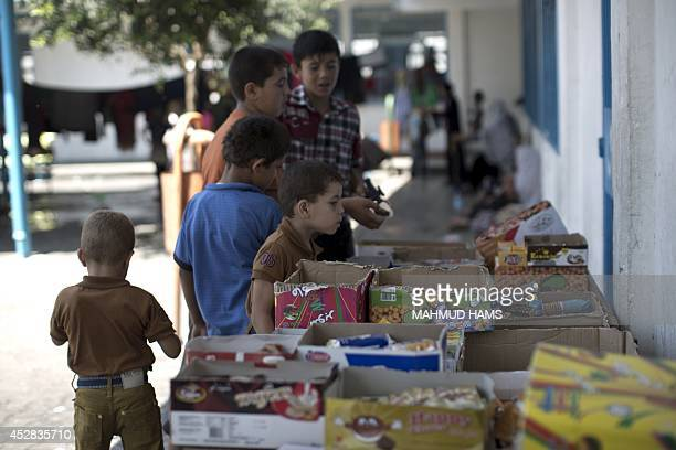 Displaced Palestinian children stand in front of a stand displaying sweets at an United Nations school in Jabalia in the northern Gaza Strip where...