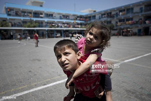 Displaced Palestinian children stand on the yard of an United Nations school in Jabalia in the northern Gaza Strip where they found refugee with...