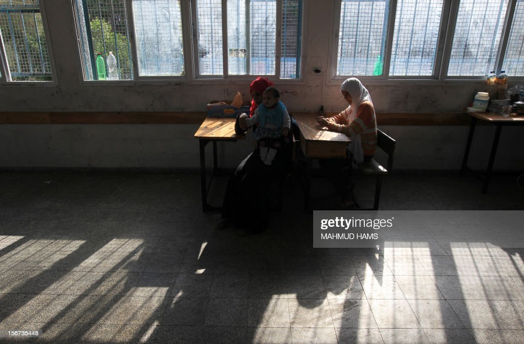 Displaced Palestinian members of the al-Attar family, who fled their house, eat breakfast as they reside in a classroom at a United Nations-run school in Gaza City on November 20, 2012. Israeli leaders discussed an Egyptian plan for a truce with Gaza's ruling Hamas, reports said, before a mission by the UN chief to Jerusalem and as the toll from Israeli raids on Gaza rose over 100.
