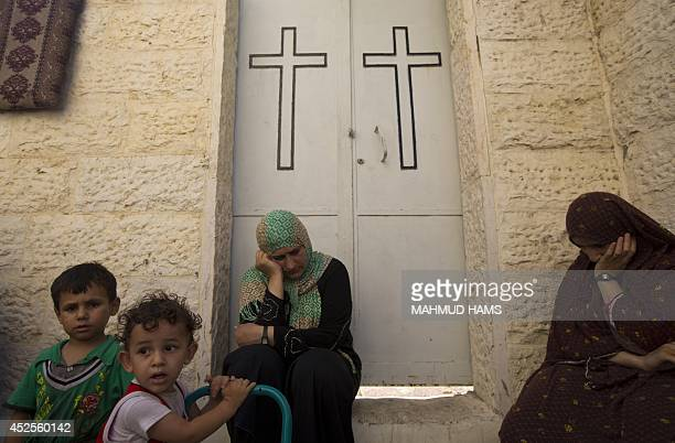 Displaced Palestinian women and children sit in a Greek Orthodox church where many Palestinians are taking shelter in Gaza City on July 23 2014 For...