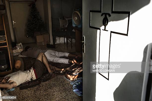 Displaced Palestinians sleep on the floor inside Gaza City's Greek Orthodox church on July 23 2014 Around 600 people mostly women and children are...