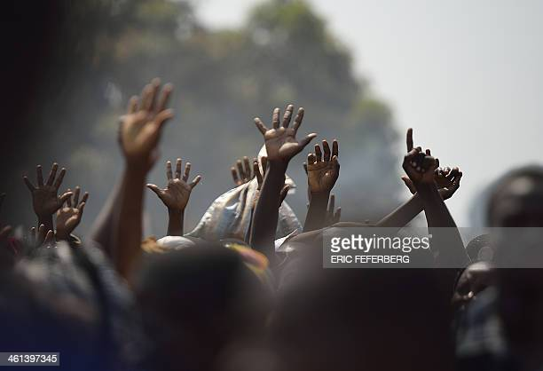 Displaced people raise their hands as they wait for food distribution near Mpoko Bangui's airport where 100000 people have found shelter on January 8...