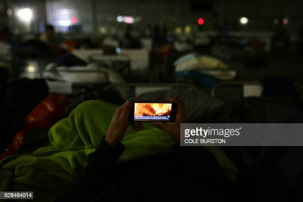 TOPSHOT A displaced person looks at the fire on their mobile phone at a makeshift evacuee center in Lac la Biche Alberta on May 5 after fleeing...