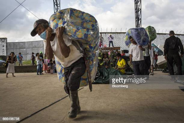 Displaced residents carry bedding to tents at a disaster relief center after landslides in Mocoa Putumayo Colombia on Monday April 3 2017 Torrential...