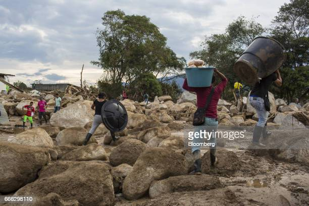 Displaced residents carry supplies through debris after a landslide in the San Miguel neighborhood of Mocoa Putumayo Colombia on Monday April 3 2017...