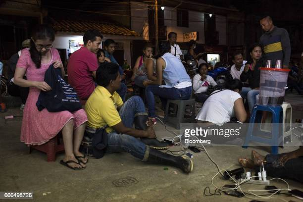 Displaced residents charger electronic devices from a gas generator after landslides after landslides in Mocoa Putumayo Colombia on Monday April 3...