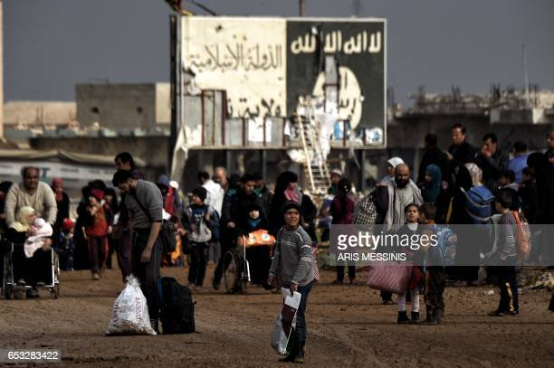 TOPSHOT Displaced residents of western Mosul evacuate the city on March 14 2017 as Iraqi government forces continue to advance in the embattled city...