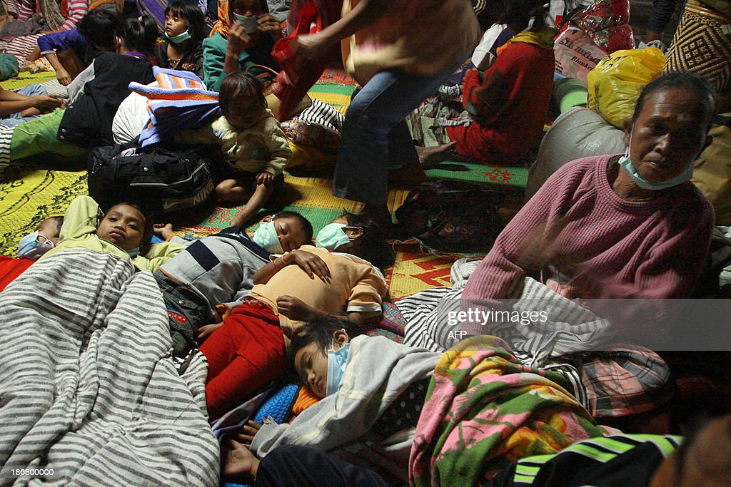 Displaced residents rest in an evacuation shelter in Karo district on Sumatra island on November 4, 2013 as Mount Sinabung volcano in western Indonesia erupted twice on November 3 hurling red-hot ash and rocks up to seven kilometres into the air and forcing more than 1,000 people to flee their homes. Mount Sinabung on Sumatra island erupted in September for the first time in three years, forcing thousands to flee their homes, and has been erupting intermittently ever since.