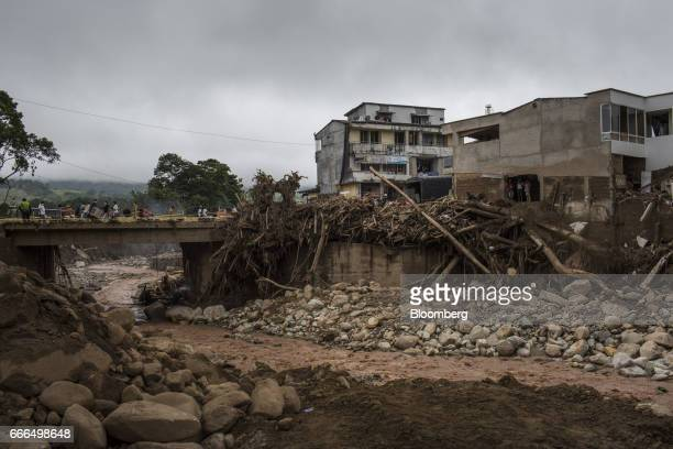 Displaced residents walk across a bridge over the Mocoa River after a landslide in Mocoa Putumayo Colombia on Monday April 3 2017 Torrential rains...