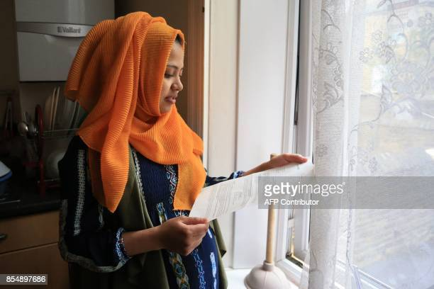 Displaced Rohingya community member Shahina Akter holds her letter of acceptance from the British Home Office granting her leave to reside in the UK...