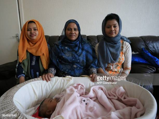 Displaced Rohingya community members Samuda Harun Omme Kulsum and sister Shahina Akter pose with Samuda's newborn baby in their family home in...