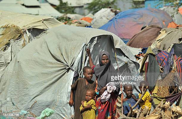 Displaced Somali children stand next to their makeshift shelters at an IDP camp on January 19 2012 during a visit to assess the progress of relief...