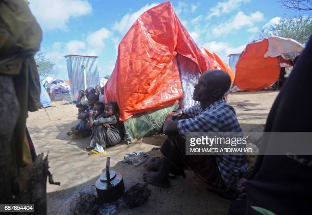 TOPSHOT Displaced Somali people sit outside makeshift tents on May 24 2017 at a camp in the Garasbaley area on the outskirts of the capital Mogadishu...