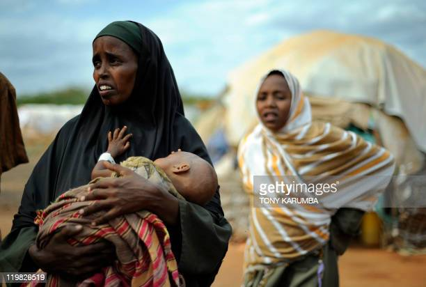 A displaced Somali refugee cradles her severely emaciated child at the Dadaab Refugee camp in eastern Kenya where the influx of Somali's displaced by...