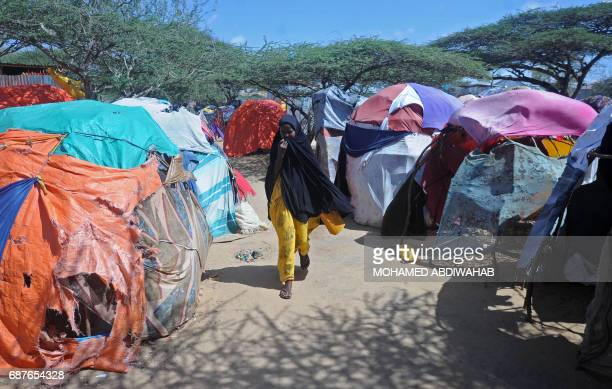 TOPSHOT A displaced Somali woman walks past makeshift tents on May 24 2017 at a camp in the Garasbaley area on the outskirts of the capital Mogadishu...